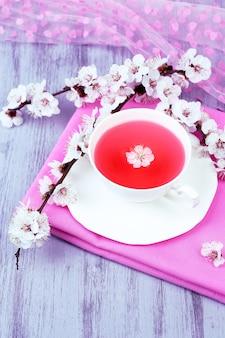 Thé parfumé avec des branches fleuries sur close-up de table en bois