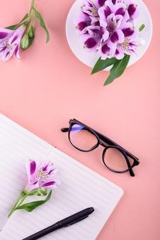 Thé parfumé dans une tasse blanche, de belles fleurs, un cahier avec un stylo et des lunettes.