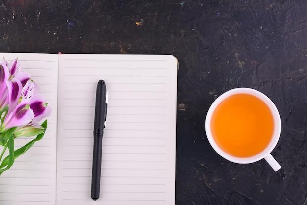 Thé parfumé dans une tasse blanche, de belles fleurs, un carnet avec un stylo et des verres.