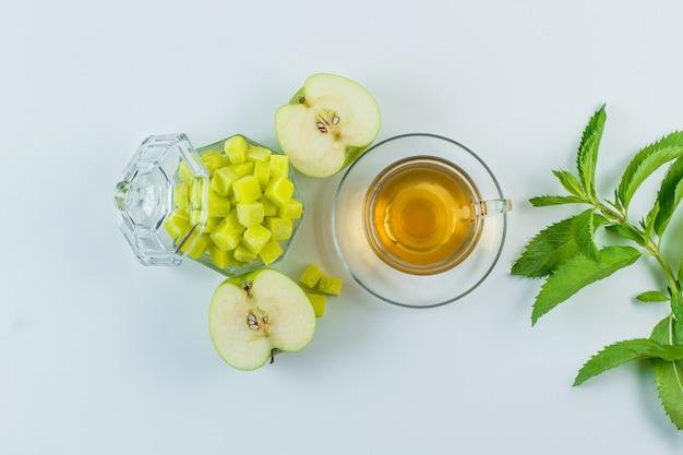 Thé à la pomme, cubes de sucre, herbes dans une tasse sur fond blanc, pose à plat.
