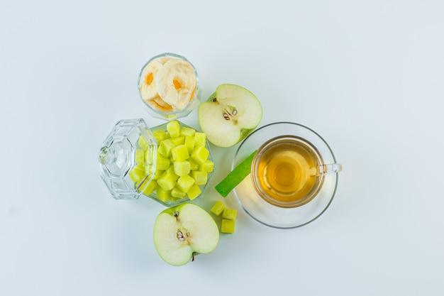 Thé à la pomme, fruits secs, cubes de sucre, bonbons dans une tasse sur fond blanc, pose à plat.