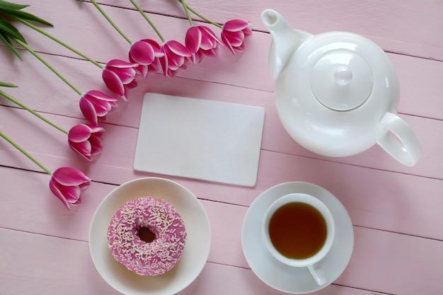 Thé de printemps.présentation à plat. liste de printemps: fleurs de tulipes roses, théière blanche, cahier vierge, tasse de thé et beignet rose.