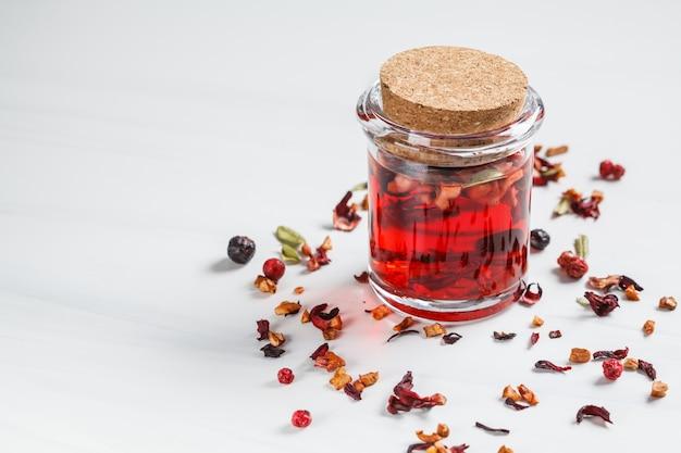 Thé rose baies aux herbes dans un bocal en verre, fond blanc. contenu de boissons saines.