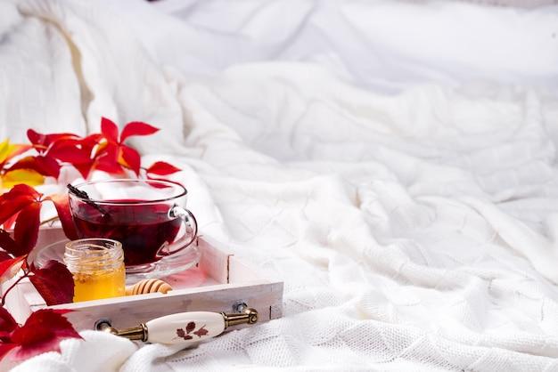 Thé rose chaud et sain sur un plateau en bois avec des feuilles mortes de l'automne sur une couverture en laine chaude et tricotée