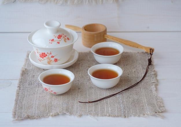 Thé rouge chinois dian hong de la province du yunnan en forme de brique pressée, gaiwan en céramique et bols avec soudure sur un tableau blanc