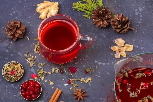 Thé rouge dans une tasse en verre parmi les pétales de feuilles de thé sec et les pommes de pin