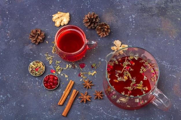 Thé rouge dans une tasse en verre et une théière parmi les pétales de feuilles de thé sec et les pommes de pin