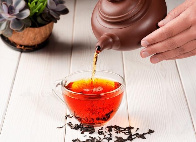 Le thé rouge est versé dans une tasse en verre de théière