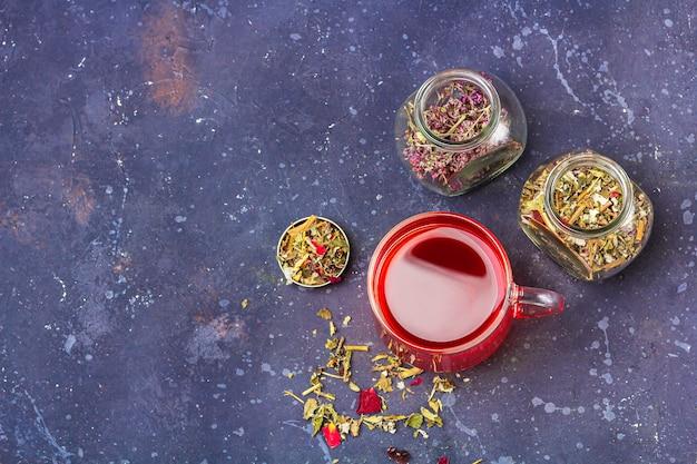 Thé rouge (rooibos, hibiscus, karkade) dans une tasse en verre et bocaux de feuilles de thé sec et pétales sur fond sombre