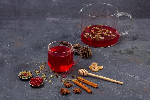 Thé rouge (rooibos, hibiscus, karkade) dans une tasse en verre et théière parmi la cannelle