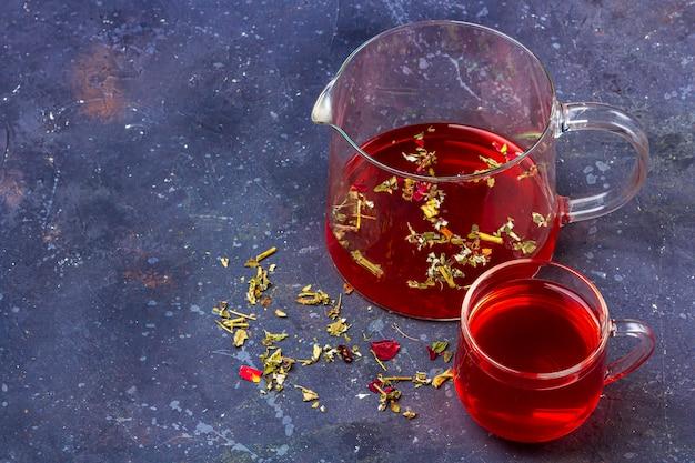 Thé rouge (rooibos, hibiscus, karkade) dans une tasse en verre et une théière parmi des feuilles de thé sèches, des pétales et des canneberges sur un fond sombre. tisane, vitamines, thé détox pour le rhume et la grippe. gros plan, copiez l'espace pour le texte