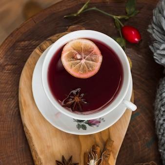 Thé rouge avec une tranche de citron sur un coussin en bois