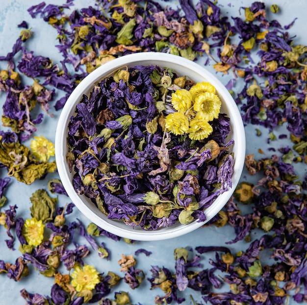 Thé sec à base de plantes aromatiques lavande et camomille en vrac près de tasse blanche sur la table en bois bleu macro