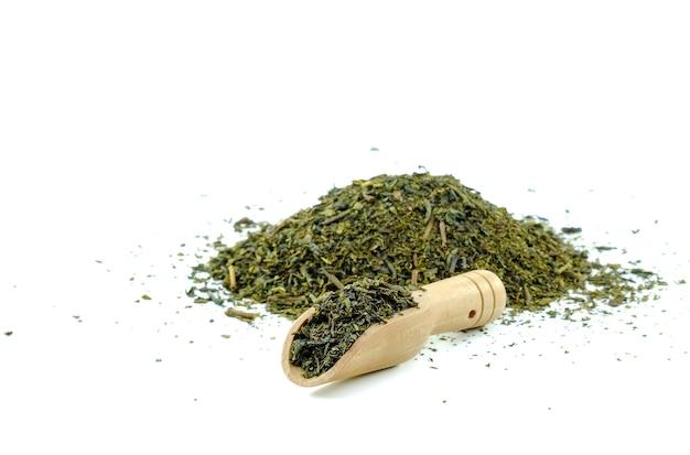 Thé sec dans une cuillère à thé en bois sur fond blanc.