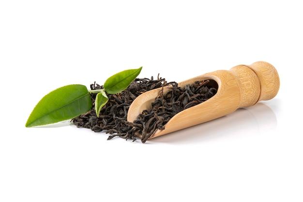 Thé sec dans des cuillères en bois avec des feuilles vertes.