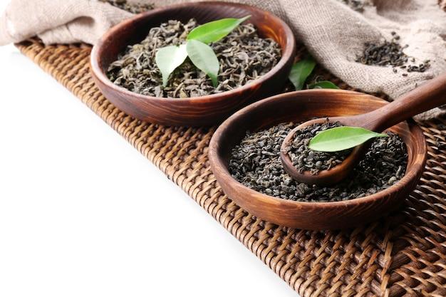 Thé sec avec des feuilles vertes dans un ustensile en bois, isolé sur blanc