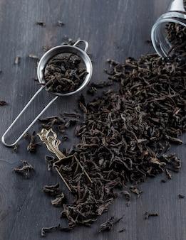 Thé sec noir dans une passoire, un pot, une cuillère sur une surface en bois vue en plongée.
