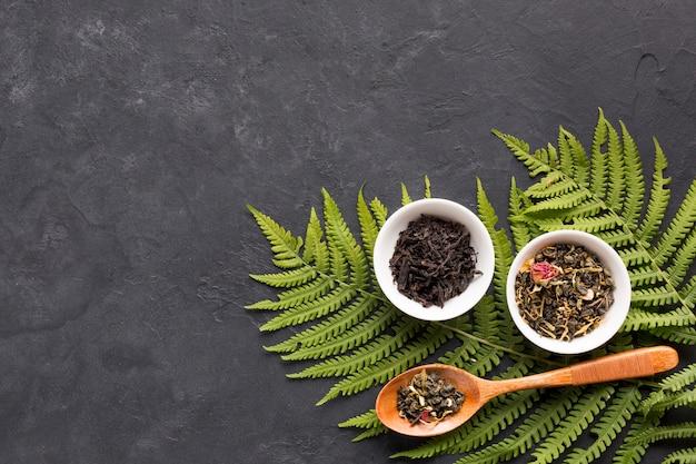 Thé séché aux herbes dans un bol en céramique avec des feuilles de fougère sur fond noir