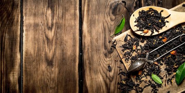 Thé séché avec des cuillères. sur table en bois.
