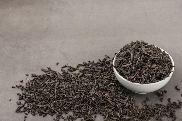 Le thé séché est versé dans une tasse en céramique blanche sur une texture grise.