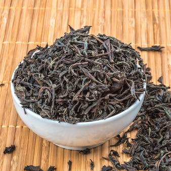 Le thé séché est versé dans une tasse en céramique sur une natte de bambou.