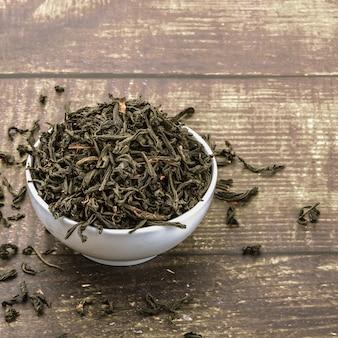 Le thé séché est versé dans une tasse en céramique sur une table en bois.
