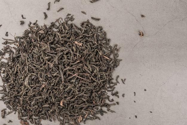 Le thé séché est versé dispersé sur un fond gris texturé.
