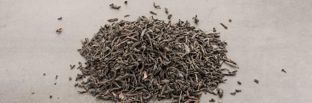 Le thé séché est versé dispersé sur un fond texturé gris.
