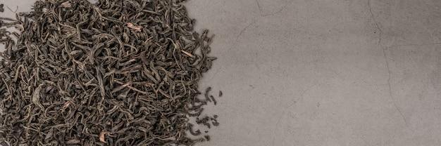 Le thé séché est versé dispersé sur une texture grise.