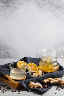 Thé en théière avec racines de gingembre et tranches de citron sur fond gris.