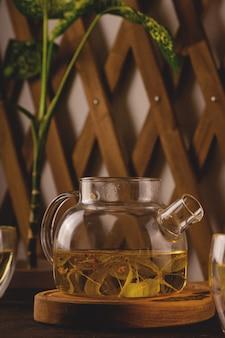Thé de tilleul dans une théière moderne sur fond sombre. minimalisme et produits biologiques sains