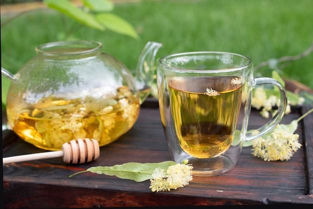 Thé de tilleul dans une théière en verre et une tasse sur un plateau en bois dans le jardin en été, tisane saine, gros plan.