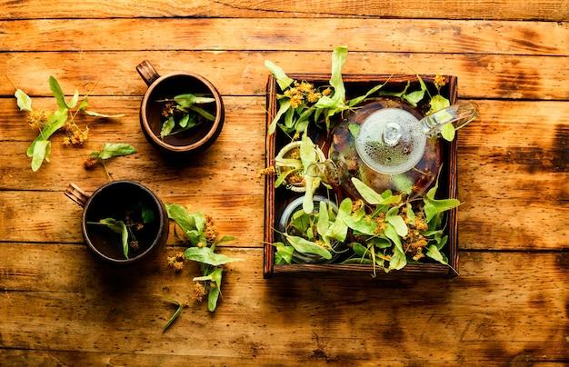 Thé de tilleul de guérison dans une théière en verre. thé naturel parfumé. phytothérapie.