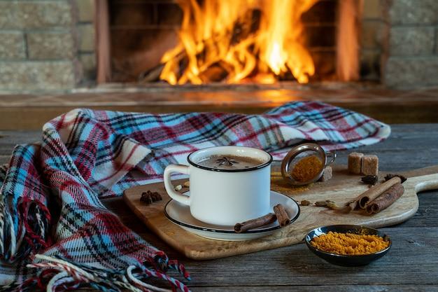 Thé traditionnel indien masala chai dans une tasse, des bâtons de cannelle et de l'anis, devant une cheminée confortable. restez à la maison et buvez une boisson saine avec du curcuma.