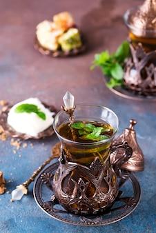 Thé turc traditionnel avec des feuilles de menthe et des bonbons dans un verre traditionnel sur du béton