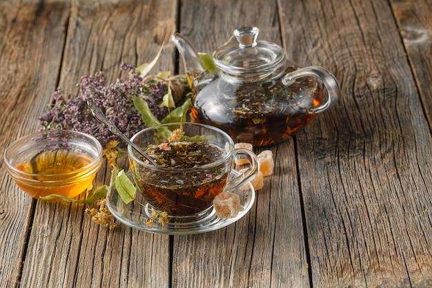 Thé utile fraîchement préparé avec des fraises des bois séchées dans une théière en verre et une tasse sur une table en bois