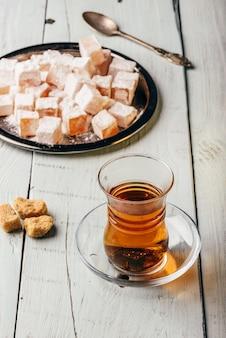 Thé en verre arabe avec délice turc rahat lokum sur une surface en bois