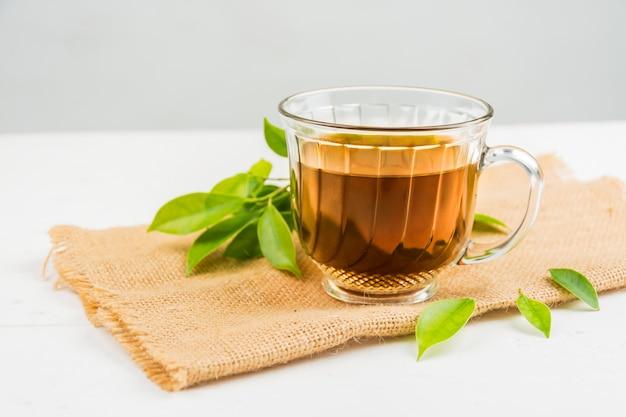 Thé avec verre à thé sur bois blanc