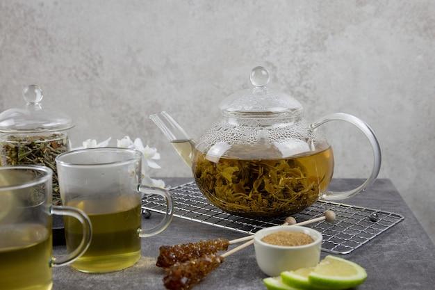 Thé vert asiatique traditionnel dans une théière en verre sur fond sombre avec des tasses à thé