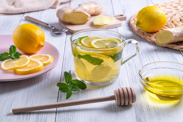 Thé vert au gingembre citronné et miel dans une tasse en verre avec des oranges autour sur une table en bois