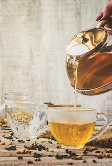 Thé vert au jasmin et noir avec citron transparent dans une petite tasse sur un fond clair. la théière mise au point sélective.