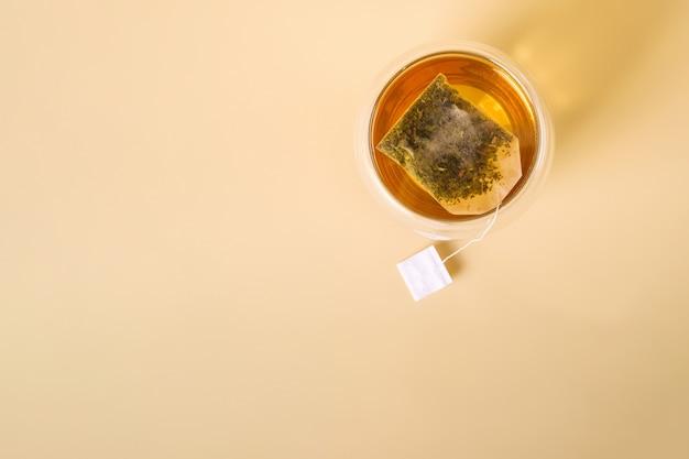 Thé vert chaud dans une tasse en verre à double paroi avec sachet de thé, vue du dessus