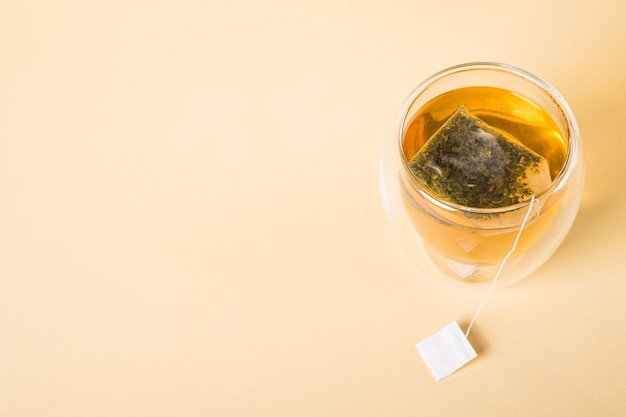 Thé vert chaud dans une tasse en verre à double paroi avec sachet de thé