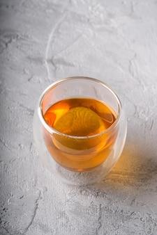 Thé vert chaud dans une tasse en verre à double paroi sur table texturée