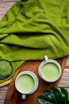 Thé vert chaud dans un verre à la crème garni de thé vert, décoré de poudre de thé vert.