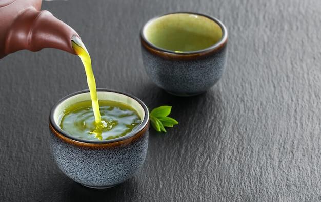 Le thé vert chaud est versé de la théière dans le bol bleu