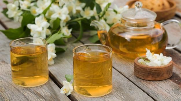 Thé vert chinois au jasmin dans des tasses et une théière sur une table en bois avec un bouquet de jasmin ...