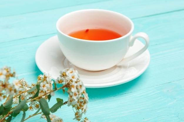 Thé vert dans une tasse en céramique avec des branches de branches d'arbres florissants