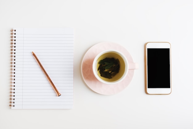 Thé vert dans une tasse rose téléphone portable et ordinateur portable avec stylo en métal sur un bureau blanc