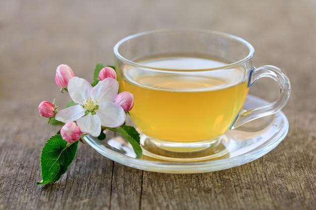 Thé vert dans une tasse en verre et fleurs
